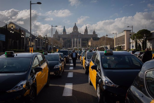 Els taxistes protesten a l'avinguda Maria Cristina de Barcelona contra el retorn d'Uber a la ciutat.