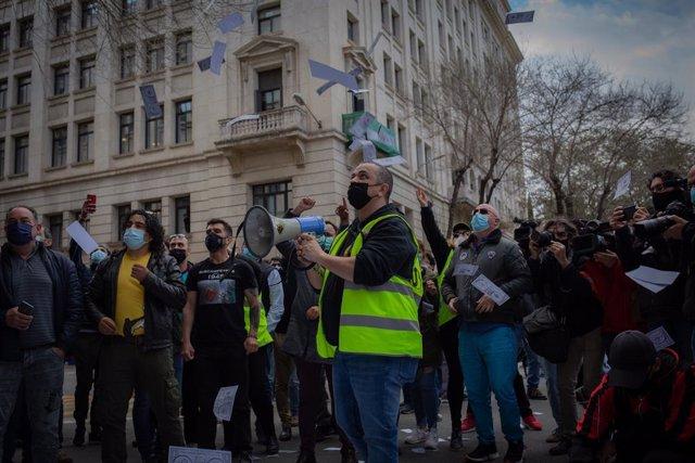 El portaveu d'Élite Taxi, Tito Álvarez, a la protesta contra Uber davant la seu de Foment del Treball, mentre els participants llancen bitllets falsos amb la cara del president de la patronal, Josep Sánchez Llibre.