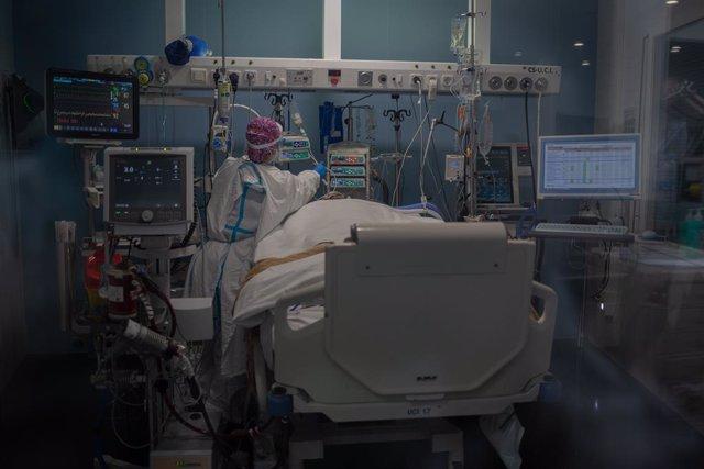 Archivo - Treballadors sanitaris protegits atenen un pacient a la UCI (Arxiu)