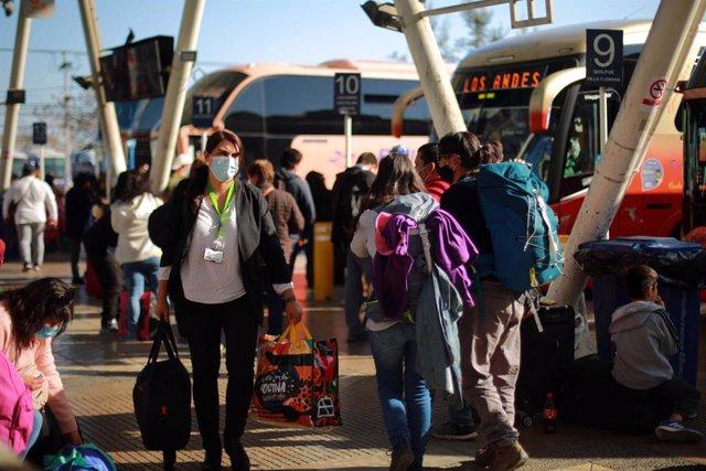 Archivo - Personas con mascarillas en una estación de autobuses en Santiago, Chile