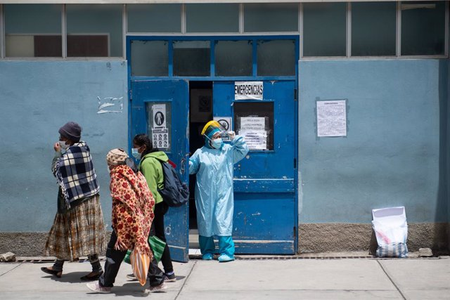 18 February 2021, Bolivia, La Paz: A health worker in a protective suit looks out from the area for receiving Covid-19 patients at Hospital de Clinicas. Doctors announced a strike until 28 February to demonstrate the health emergency health law that restr