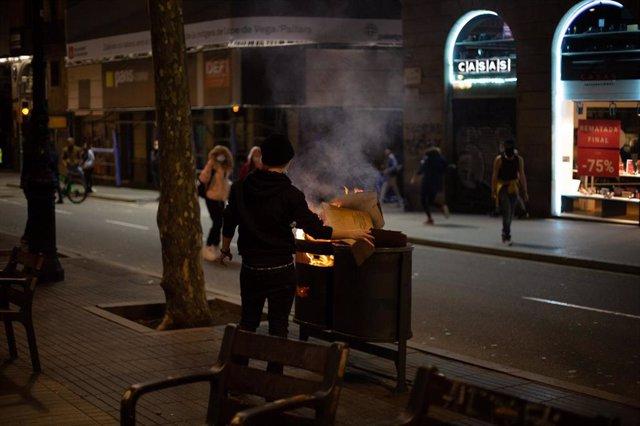 Un activista quema una papelera de La Rambla de Barcelona en los disturbios en apoyo al rapero Pablo Hasel