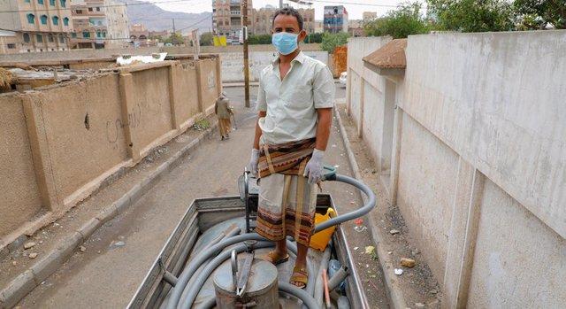Archivo - Un hombre trabaja en un camión que facilita agua limpia en Saná.