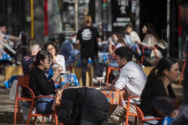 Personas en la terraza de un bar en Sevilla