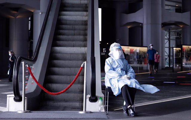 17 March 2021, China, Hong Kong: A medical worker wearing a personal protective equipment suit (PPE) sits next to an escalator at HSBC headquarters in Hong Kong. HSBC Holdings Plc's main Hong Kong office have been closed until further notice after multipl