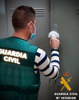 Un agente de la Guardia Civil toma unas huellas en una taquilla