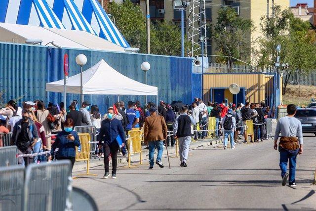 Archivo - Varias personas esperan en una cola para tramitar papeles de Extranjería en el Centro de Internamiento de Extranjeros (CIE) de Aluche