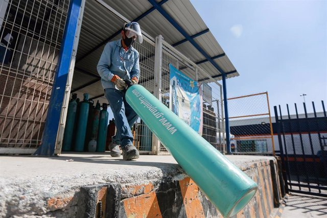 Archivo - Un trabajador carga un cilindro de oxígeno en un almacén.