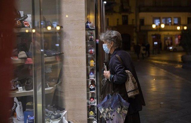 Una persona observa el escaparate de un comercio. Andalucía amplía hasta las 21.30 horas la apertura de hostelería y comercio en municipios con nivel 2 de alerta. En Sevilla (Andalucía, España), a 05 de marzo de 2021.