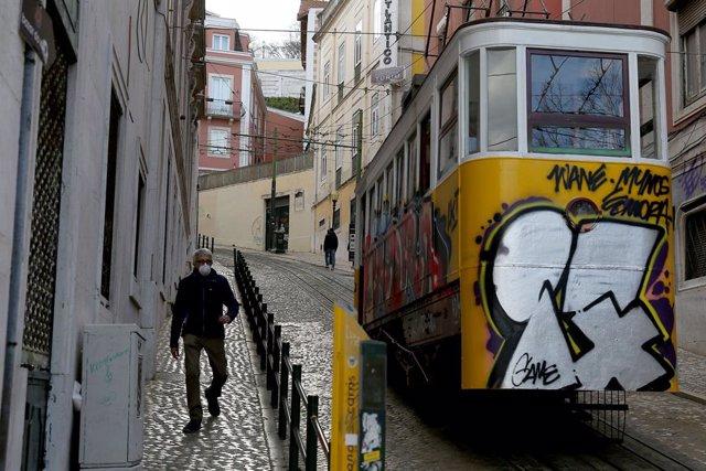 Archivo - Un hombre con mascarilla junto a un tranvía de Lisboa