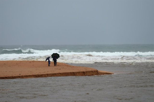 20 March 2021, Australia, Sydney: People stand on the edge of Narrabeen Lagoon and Narrabeen Beach. After days of heavy rain showers, the Bureau of Meteorology issued a severe weather warning for people in the state of New South Wales and warned of potent