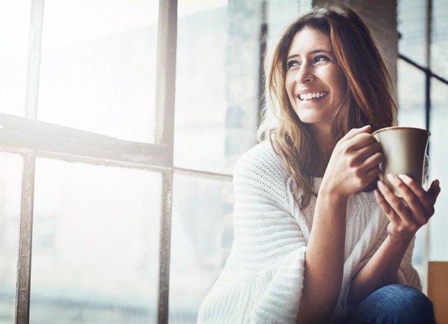 Archivo - Mujer sonriendo junto a una ventana con una taza.