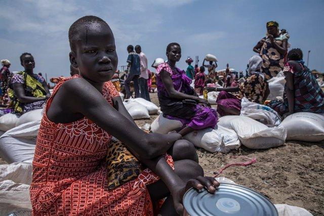 Archivo - Una mujer recibe asistencia alimentaria en Sudán del Sur