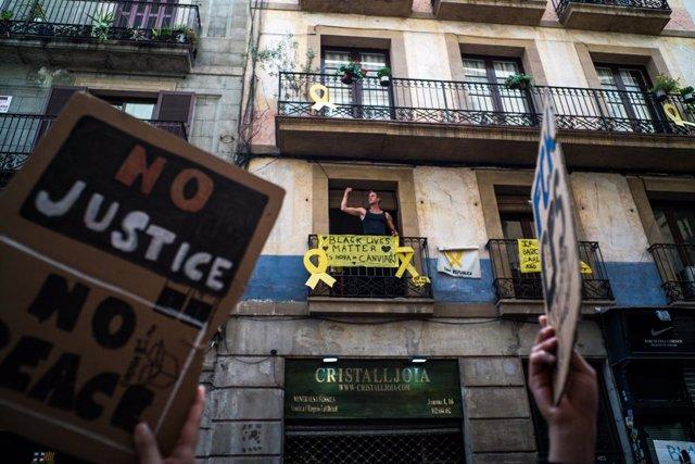 Archivo - Un hombre se asoma a su balcón del que cuelga una pancarta en la que se lee 'Black Lives Matter' durante una concentración en Plaza de Sant Jaume de Barcelona contra el racismo 'Las vidas negras importan' organizada por  la Comunidad Negra Afric