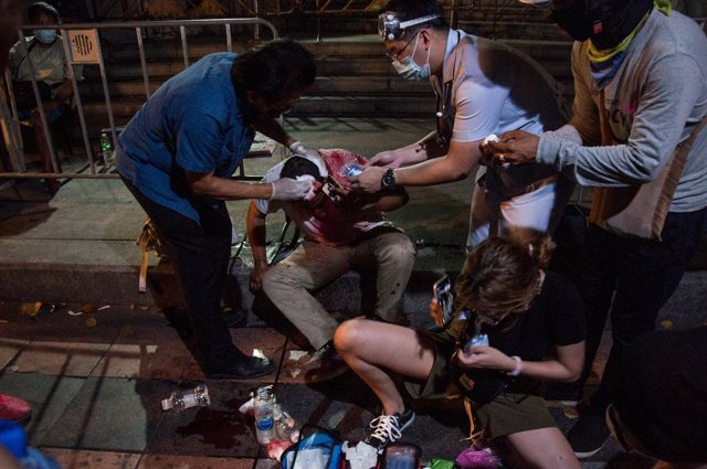 20 March 2021, Thailand, Bangkok: Protesters give first aid to a colleague who was injured during clashes at a pro-democracy protest near the Grand Palace demanding the resignation of Thai Prime Minister Chan-o-cha and reform of the monarchy. Photo: Peera