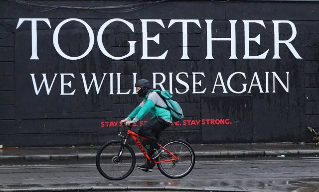 Archivo - Un ciclista pasa ante un mural por el centro de Dublín