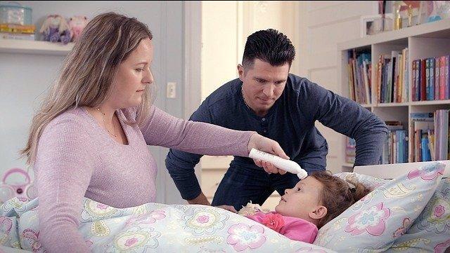 Archivo - Familia cuidando a su hija enferma. Termómetro.