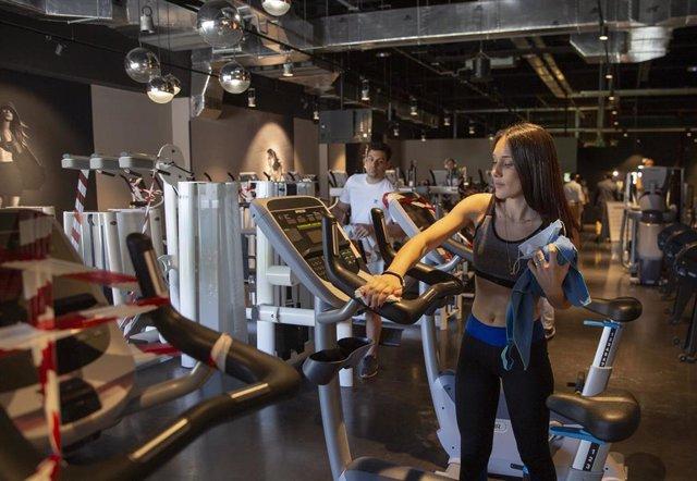 Archivo - Un usuario limpia una máquina tras hacer ejercicio en el gimnasio McFit durante el primer día de la fase 3, donde se permite la reapertura de gimnasios con el 50 % del aforo y manteniendo las medidas de seguridad,. En Sevilla, a 08 de junio de 2