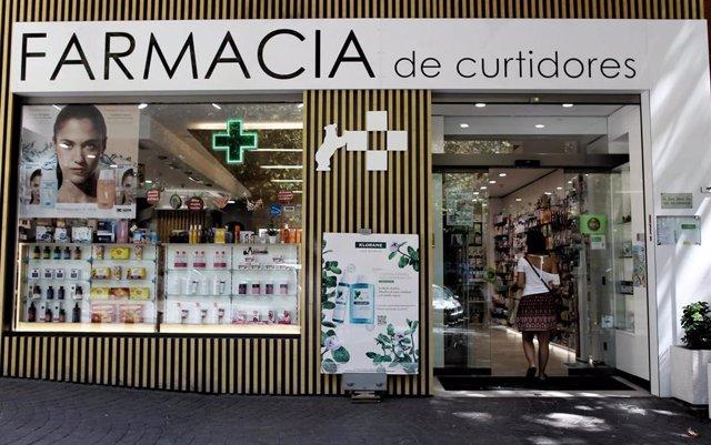 Archivo - Una mujer entra en una farmacia.
