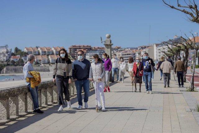 Varias personas caminan por un paseo marítimo en Sanxenxo, Pontevedra, Galicia (España), a 21 de marzo de 2021. El pasado miércoles el Ministerio de Sanidad y las Comunidades Autónomas acordaron una serie de medidas a aplicar durante el puente de San José