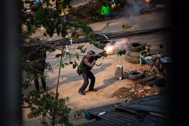 13 March 2021, Myanmar, Yangon: Myanmar police officer shoots towards the demonstrators during a protest against the military coup. Photo: Theint Mon Soe/SOPA Images via ZUMA Wire/dpa