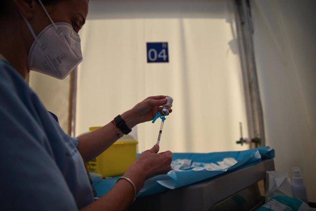 Una profesional sanitaria sostiene una jeringuilla y un vial con la vacuna contra la Covid-19 de AstraZeneca en el Hospital de campaña de La Fe, en Valencia, Comunidad Valenciana (España), a 15 de marzo de 2021.