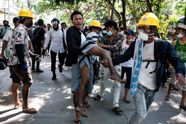 19 March 2021, Myanmar, Yangon: Demonstrators carry a wounded man during clashes at a protest against the military coup and the detention of civilian leaders. Photo: Aung Kyaw Htet/SOPA Images via ZUMA Wire/dpa