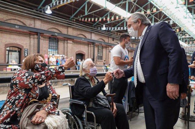 El presidente de Argentina, Alberto Fernández, saludando a un grupo de personas que esperan ser vacunadas contra la COVID-19.