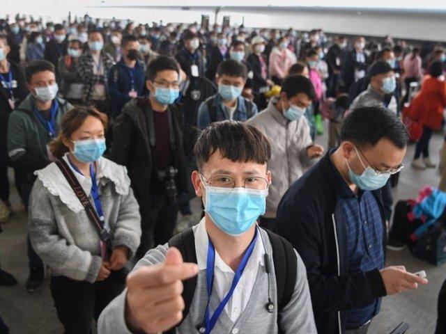 Archivo - Migrantes con mascarilla en Hubei, China
