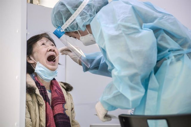 Archivo - 23 January 2021, China, Hong Kong: A health worker wearing a protective suit takes a swab sample from a woman in a test truck during lockdown imposed by the government to curb the spread of the pandemic. Photo: Ivan Abreu/SOPA Images via ZUMA Wi