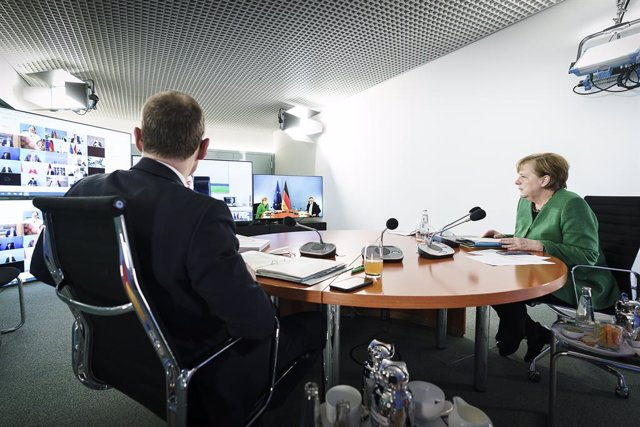 HANDOUT - 22 March 2021, Berlin: German Chancellor Angela Merkel (R) and Governing Mayor of Berlin Michael Mueller participate in a video conference with the German Minister Presidents to discuss the latest updates regarding the coronavirus pandemic. Phot
