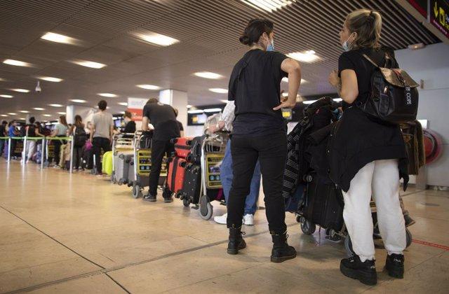 Archivo - Pasajeros con maletas hacen cola para facturar en la Terminal T1 del Aeropuerto Adolfo Suárez Madrid-Barajas el día de su apertura y de las fronteras de España, en Madrid (España), a 1 de julio de 2020. Las compañías aéreas han programado 1.482