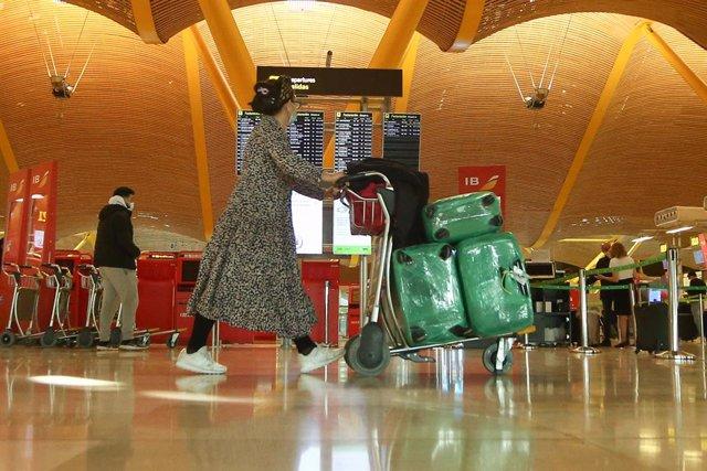 Una mujer camina con varias maletas en un carro en la terminal T4 del Aeropuerto Adolfo Suárez Madrid-Barajas, en Madrid (España), a 15 de marzo de 2021. El Gobierno ha prorrogado hasta el próximo 30 de marzo la limitación de los vuelos directos y buques