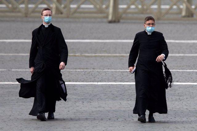Dos religiosos caminan por la plaza San Pedro en El Vaticano.