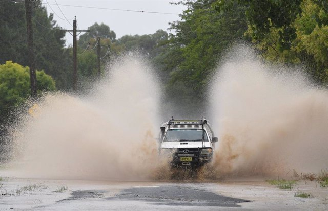 20 March 2021, Australia, Sydney: A car drives through a closed road at Yarramundi Lane. After days of heavy rain showers, the Bureau of Meteorology issued a severe weather warning for people in the state of New South Wales and warned of potentially life-
