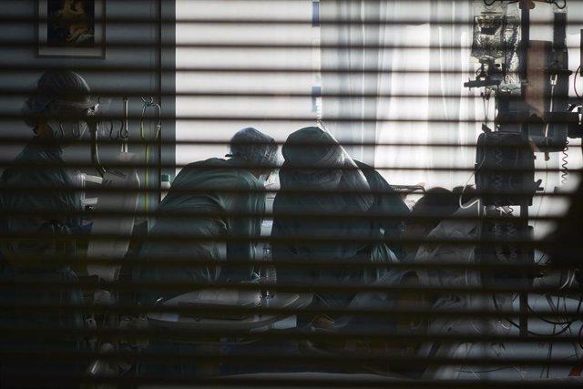 Archivo - Dps trabajadores sanitarios totalmente protegidos atienden a un paciente en una camilla de la UCI de la Clínica Universidad de Navarra, en Pamplona, Navarra, (España), a 10 de noviembre de 2020. La situación actual de las UCI, ahora que la regió