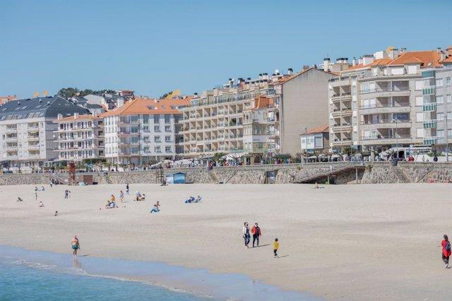 Varias personas pasean por la playa de Sanxenxo, Pontevedra, Galicia (España), a 21 de marzo de 2021.