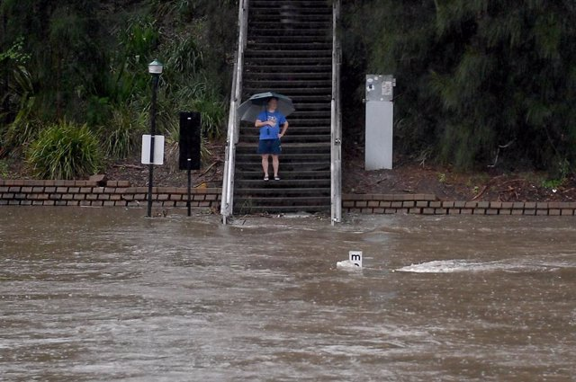 20 March 2021, Australia, Sydney: A man watches the Parramatta river breaking its banks at the Charles St weir and ferry wharf, due to heavy rains. The Bureau of Meteorology issued a severe weather warning for people in the state of New South Wales and wa