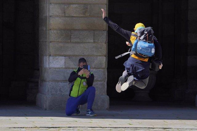 Un peregrino se fotografía saltando en la Catedral de Santiago durante el puente de San José, en Santiago de Compostela, en A Coruña, Galicia (España), a 20 de marzo de 2021.