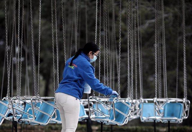 Una operaria de la limpieza desinfecta `las sillas voladoras del Parque de Atracciones durante el Día del Padre, en Madrid (España), a 19 de marzo de 2021. El Parque de Atracciones reabrió el pasado 6 de marzo con un aforo limitado del 60%, una distancia