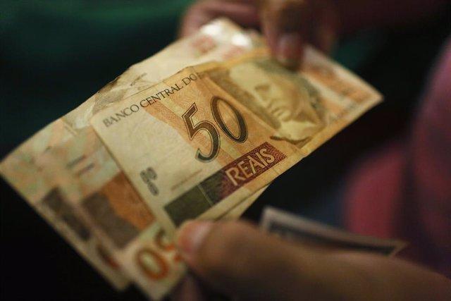 Archivo - Un billete de 50 reales brasileños