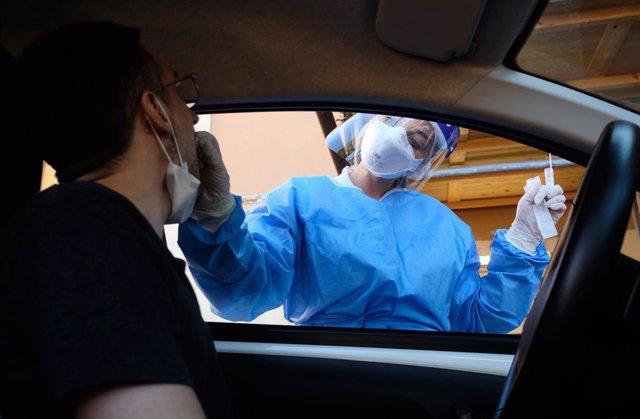 Archivo - Una trabajadora sanitaria realiza una prueba de coronavirus a un ciudadano en Italia