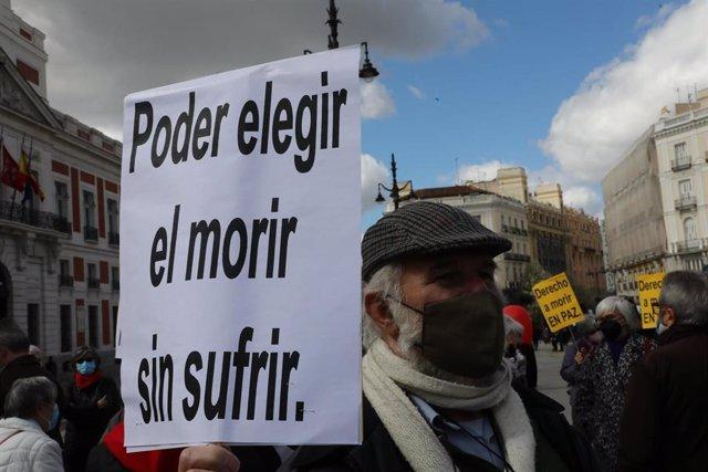 Un hombre con un cartel en el que se lee: `Poder elegir el morir sin sufrir durante una concentración de Derecho a Morir Dignamente en la Puerta del Sol, en Madrid (España), a 18 de marzo de 2021. Derecho a Morir Dignamente se manifiesta para dar apoyo a