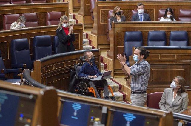 La ministra de Trabajo, Yolanda Díaz, aplaude al vicepresidente segundo del Gobierno, Pablo Iglesias (d), durante una sesión plenaria en el Congreso de los Diputados, Madrid, (España), a 24 de marzo de 2021.