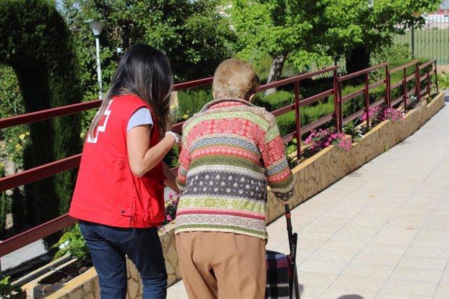Una voluntària de la Creu Roja acompanya a una persona gran.
