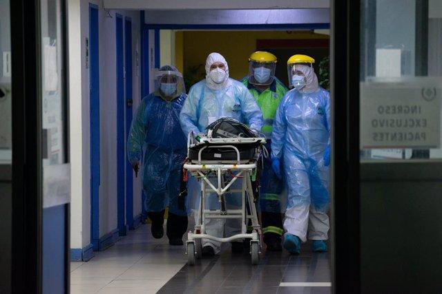 Sanitarios trasladando a un paciente en cuidados intensivos por coronavirus