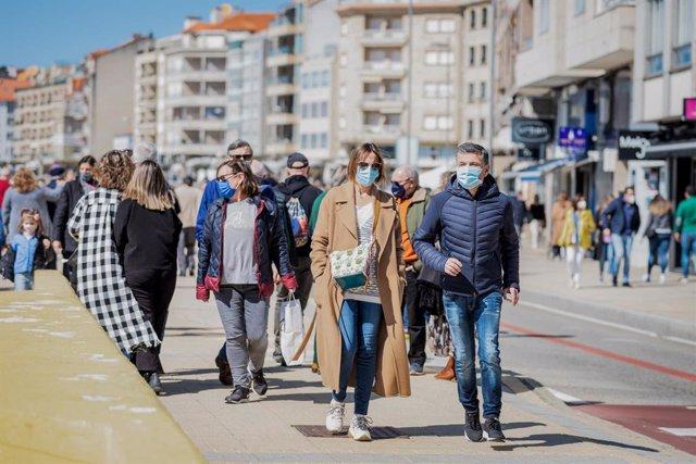 Varias personas pasean por el paseo marítimo de Sanxenxo, Pontevedra, Galicia (España), a 21 de marzo de 2021. El pasado miércoles el Ministerio de Sanidad y las Comunidades Autónomas acordaron una serie de medidas a aplicar durante el puente de San José.