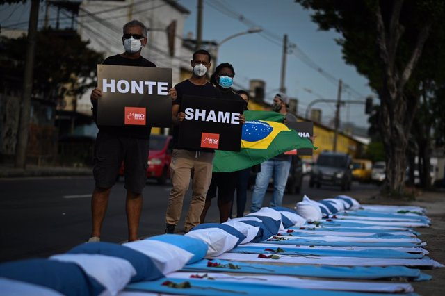 24 March 2021, Brazil, Acari: Demonstrators from the NGO Rio de Paz hold up placards outside Ronaldo Gazzola Hospital next to stretchers with sheets, pillows and roses during a protest in memory of the approximately 300,000 Coronavirus deaths in Brazil. P