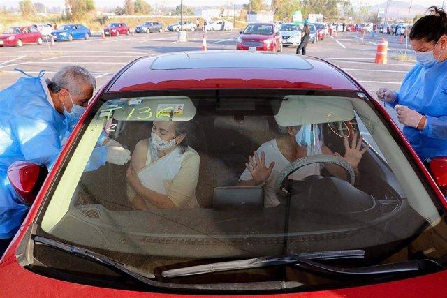 Dos personas reciben la vacuna contra la COVID-19 en su coche, en Tonala, México.