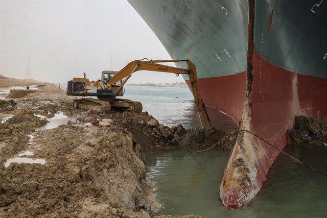 Trabajos de una excavadoras para liberar el buque 'Ever Given', encallado en el canal de Suez